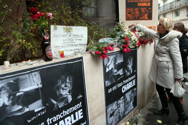 Mourners lay flowers to remember victims of the terror attack at Charlie Hebdo, near the newspaper's office building in Paris, France, on January 8, 2015. File Photo by Maya Vidon-White/UPI