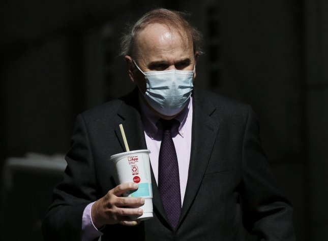 A pedestrian wears a face mask to prevent spread of COVID-19, which causes symptoms in 4 out of every 5 people who get it, while walking in Lower Manhattan in New York City on Monday. Photo by John Angelillo/UPI