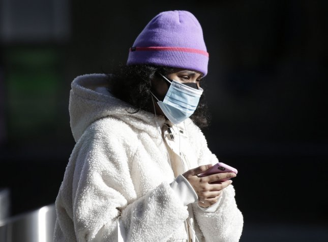 Pedestrians wear face masks to protect from and to prevent the spread of COVID-19 as they walk in Times Square in New York City, on January 10, 2021. File Photo by John Angelillo/UPI