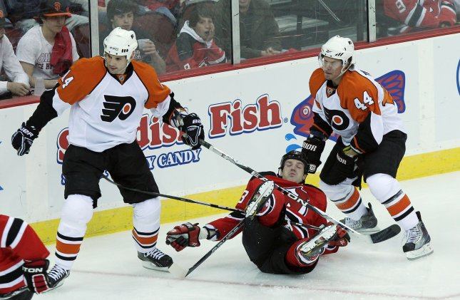 New Jersey Devils David Clarkson falls between Philadelphia Flyers Kimmo Timonen (44) and Ian Laperriere in the first period in game 1 round 1 of the Stanley Cup Playoffs at Prudential Center in New Jersey on April 14, 2010. UPI/John Angelillo