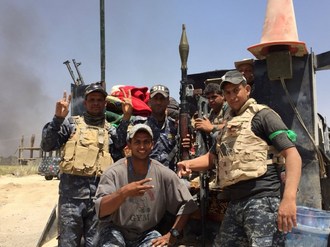 Soldiers of Iraqi government forces flash victory signs after recapturing the town Zankoura from the Islamic State (IS) jihadist group, northwest of Ramadi, in Anbar province, June 16, 2016. A similar celebration took place Sunday when the Iraqi army declared it had freed Falluah of Islamic State. Photo by Abbas Mohammed /UPI