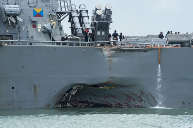 Damage to the portside is visible as the guided-missile destroyer USS John S. McCain steers toward Changi Naval Base, Singapore, on August 21 following a collision with the merchant vessel. File Photo by MC2 Joshua Fulton/U.S. Navy