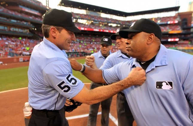 Home plate umpire Angel Hernandez (L) returns the good luck tap to the chest to first base umpire Adrian Johnson prior to a game in St. Louis. UPI/Bill Greenblatt