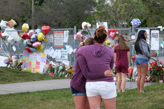 Students grieve outside of Marjory Stoneman Douglas High School in Parkland, Fla., Monday, where 17 people were killed in a shooting attack last week. Photo by Gary Rothstein/UPI