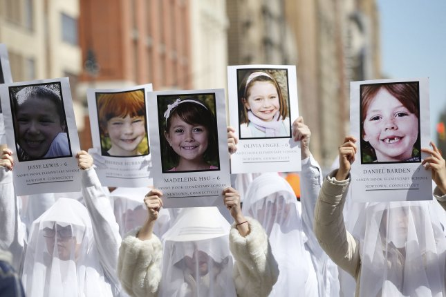 Marchers hold up photos of victims of the Sandy Hook Elementary School shootings at the March for Our Lives demonstration in New York City in 2018. The Supreme Court will allow the lawsuit against gunmaker Remington to proceed. However, Justices will not take up the case. Photo by John Angelillo/UPI