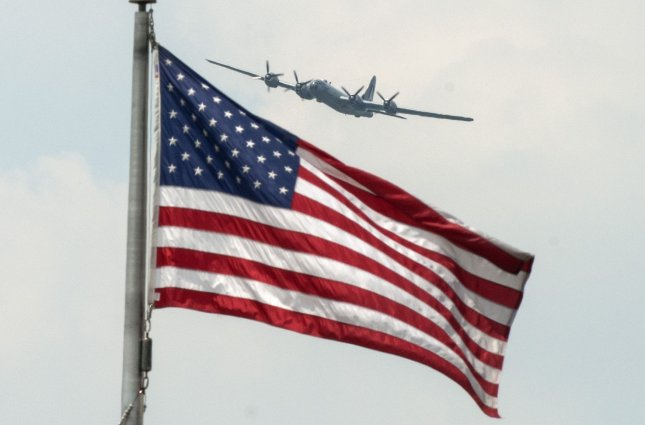 A B-29 Superfortress flies above the American flag during a World War II anniversary event in Washington May 8, 2015. The Stars and Stripes officially became the flag of the United States on June 14, 1777. File Photo by Pat Benic/UPI