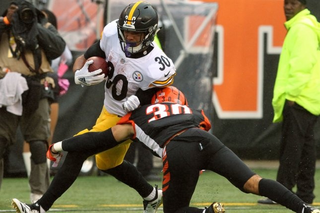 Pittsburgh Steelers running back James Conner (30) fights to break free from the Cincinnati Bengals' Jessie Bates (30) during the second half at Paul Brown Stadium in Cincinnati, Ohio, October 14, 2018. Photo by John Sommers II /UPI