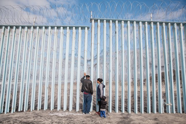 Migrant refugees look through the border fence separating the United States and Mexico at Playas de Tijuana in Tijuana, Mexico. File Photo by Ariana Drehsler/UPI