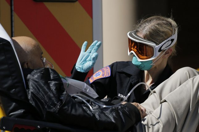 A healthcare worker takes care of a patient that arrived in an ambulance at Wyckoff Heights Medical Center in April 2020 in New York City. File Photo by John Angelillo/UPI