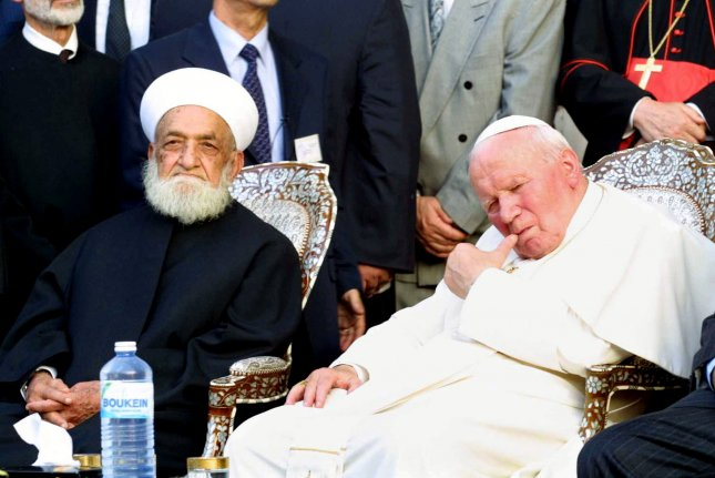 Syria's Mufti Sheikh Ahmad Kuftaro (L) meets Pope John Paul II at the Great Umayyad Mosque in Damascus' old city where the Tomb of Saint John Baptist is located May 6, 2001. Pope John Paul made history by becoming the first pontiff ever to enter a mosque and urged Christians and Muslims to forgive each other for the past. File Photo by Khaledal-Hariri/UPI