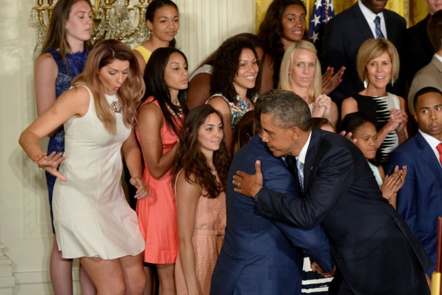University of Connecticut star basketball player Stefanie Dolson (L) slips off the podium riser as U.S. President Barack Obama hugs head coach Geno Auriemma during a presentation in the East Room of the White House in Washington, DC on June 9, 2014. Obama honored both the women's and men's basketball teams from the University of Connecticut as they both won the NCAA collegiate basketball championships for the 2013-2014 season. UPI/Pat Benic