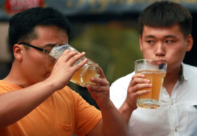 Chinese men compete in a beer drinking contest in downtown Beijing on June 26, 2014. In California, people who drank too much will be able to get a free ride home from the bar under a new law set to take effect on Jan. 1. File Photo by Stephen Shaver/UPI