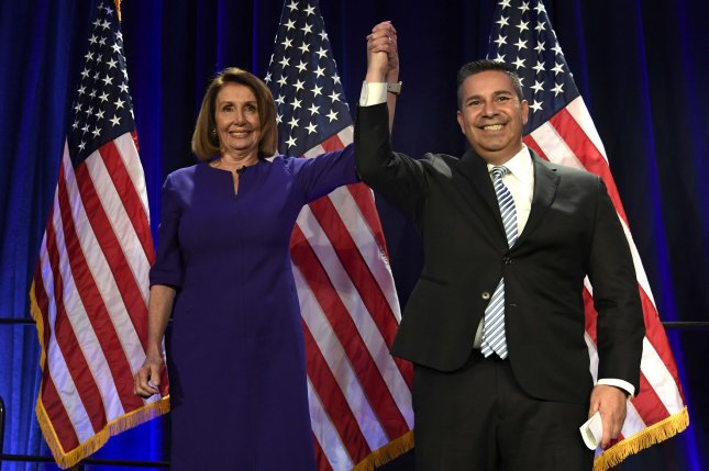 House Democratic leader Nancy Pelosi of California joins hands with Democratic Congressional Campaign Committee Chairman Ben Ray Lujan as she arrives to address a watch party on Tuesday in Washington, D.C. Photo by Mike Theiler/UPI