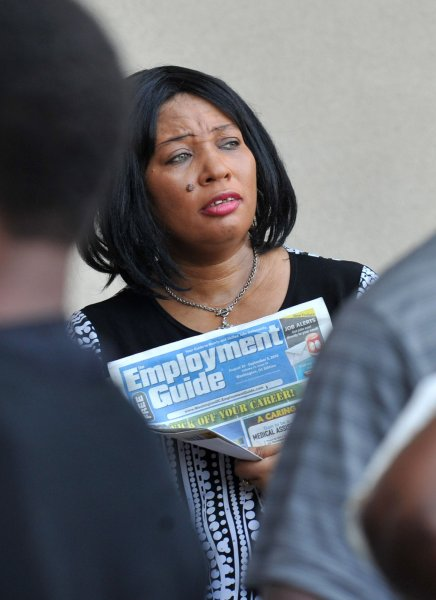 A job seeker holds an employment guide as she waits in line for the Metro DC Diversity Job Fair at FedEx Field in Landover, Maryland on August 31, 2010. UPI/Kevin Dietsch