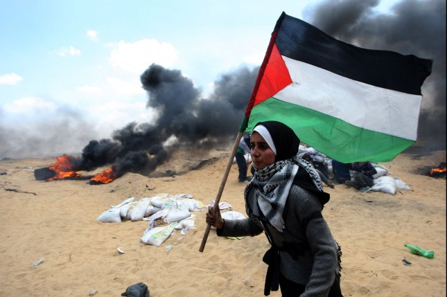 A Palestinian woman carries the Palestinian flag on May 14 during a protest opposing the opening of the new U.S. Embassy in Jerusalem. Australia is considering a similar move. Photo by Ismael Mohamad/UPI