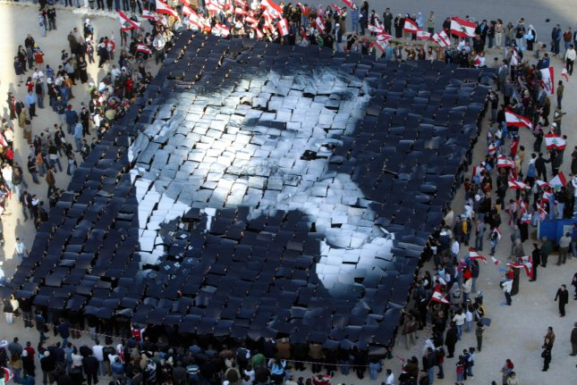 Lebanese people assemble a large montage of former prime minister Rafik al-Hariri near his grave at Beirut's Martyrs' Square, March 26, 2005. (UPI File Photo/Mahmoud Tawil)