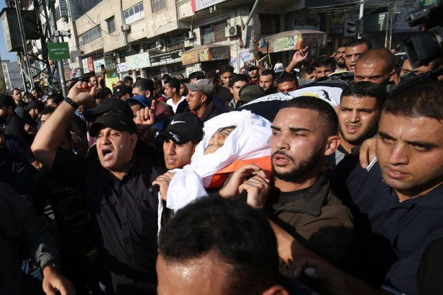 Mourners chant slogans as they carry the body of Palestinian Islamic Jihad senior leader Baha Abu al-Ata during his funeral in Gaza City on Tuesday. Israel's military killed the commander in a targeted strike on his home in the Gaza Strip, prompting retaliatory rocket fire and fears of a severe escalation in violence. Photo by Ismael Mohamad/UPI