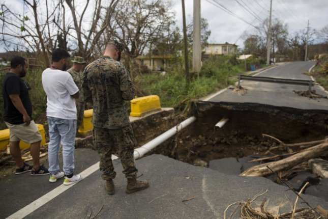 A Marine Corps infantry officer talks to residents in Ceiba, Puerto Rico, on October 2 about a damaged road caused by flooding from Hurricane Maria. Photo by Cpl. Juan Soto-Delgado/USMC/UPI