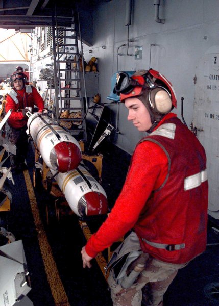Airman David Rodriguez (R) prepares cluster bombs aboard the aircraft carrier USS Independence on February 12, 1998. On August 1, 2010, a worldwide ban on cluster bombs went into effect. File Photo by Felix Garza/U.S. Navy