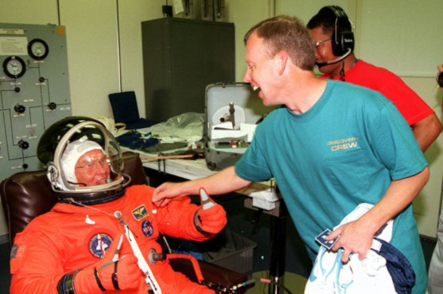 Pilot Steven W. Lindsey (R) reaches playfully for the name tag on the flight suit of Payload Specialist John H. Glenn Jr., on October 29, 1998. File Photo courtesy of NASA