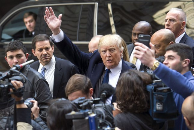 Republican presidential candidate Donald Trump waves as he takes members of the media on a walking tour at the construction site of his Trump International Hotel at the Old Post Office Building in Washington, D.C. on March 21. Photo by Kevin Dietsch/UPI