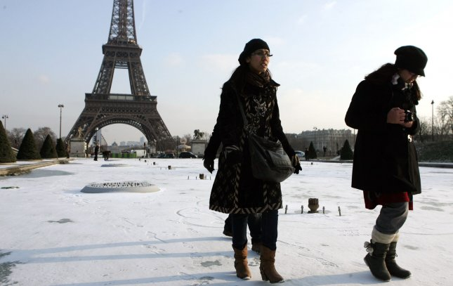 Tourists walk on the frozen waters of the Trocadero fountain in Paris facing the Eiffel Tower, in Paris, February 08, 2012. A cold snap has been sweeping across Europe with sub-zero temperatures, claiming more than 220 lives. UPI/Eco Clement