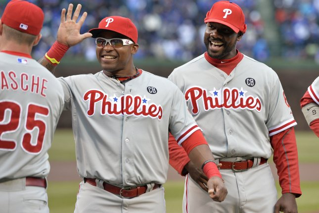 Philadelphia Phillies' Ryan Howard (R-L) and Marlon Byrd (3) high-five Cody Asche before the Chicago Cubs' home opener at Wrigley Field on April 4, 2014 in Chicago. UPI/Brian Kersey