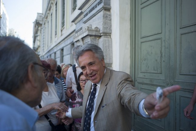 People are given priority tickets by a National Bank branch manager as they wait to enter the bank in Athens, Greece, on Monday. Photo by Dimitris Michalakis/UPI