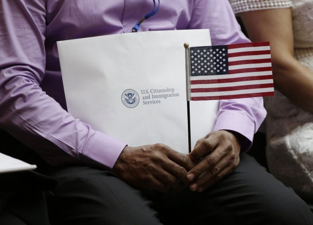 New Citizens of the United States of America hold American Flags when U.S. Citizenship and Immigration Services (USCIS) administer the Oath of Allegiance to America's newest citizens during a special naturalization ceremony at the Stephen A. Schwarzmann Building of the New York Public Library in New York City on July 1, 2016. The USCIS announced premium processing for H-1B visas will be suspended beginning April 6 and may last for up to six months.