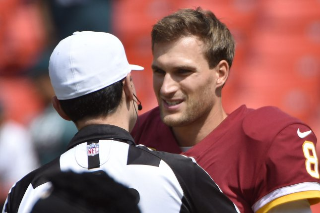 Washington Redskins quarterback Kirk Cousins (R) talks to referee Brad Allen (L) during warmups prior to an NFL game on September 10 at FedEx Field in Landover, Md. Photo by David Tulis/UPI