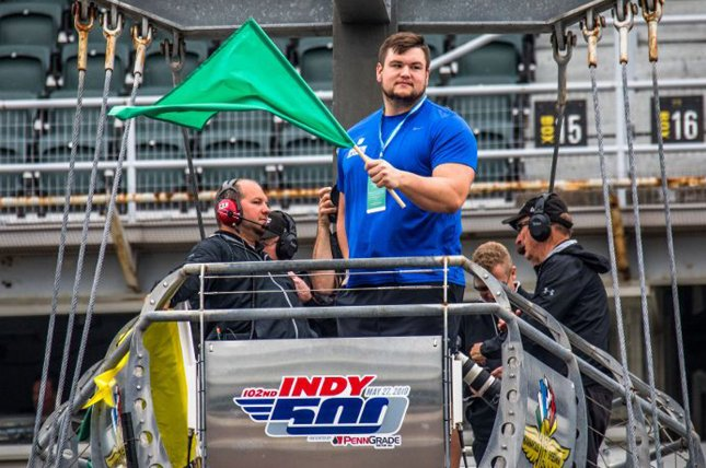 Indianapolis Colts first round pick Quenton Nelson waves the green flag to start practice during fast Friday practice for the 102nd Indianapolis 500 on May 18 at the Indianapolis Motor Speedway in Indianapolis. Photo by Ed Locke/UPI
