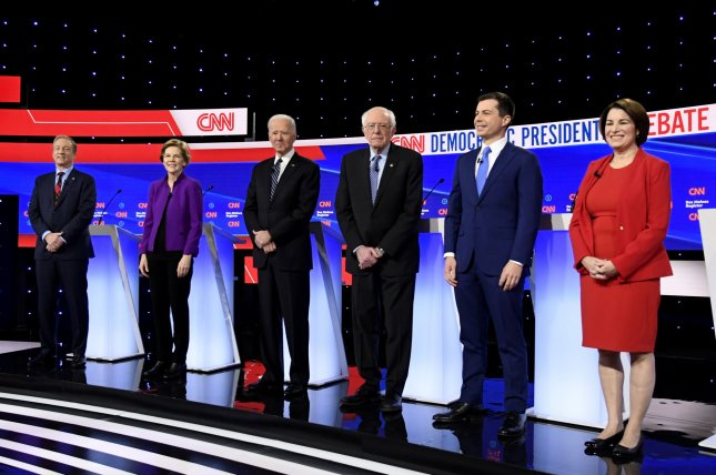 From left to right, 2020 Democratic presidential candidates Tom Steyer, Elizabeth Warren, Joe Biden, Bernie Sanders, Pete Buttigieg and Amy Klobuchar gather onstage for a debate in Des Moines, Iowa on Tuesday. Photo by Mike Theiler/UPI
