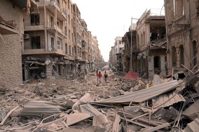 In a photo released by Syria's official news agency, SANA, Syrians walk through rubble where multiple bombs hit the center of Aleppo, Syria on October 3, 2012. UPI
