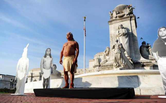 Performance artist James Luna waits to have his picture taken during his piece titled Take a Picture With a Real Indian, in front of the Christopher Columbus Statue on Columbus Day in Washington on October 11, 2010. In the piece Luna invites members of the audience to pose with him as he confronts commonly held perceptions of Natives Americans. Phoenix joined a host of other cities who have voted to celebrate Indigenous Peoples' Day on the second Monday of November, the same day as Columbus Day. File Photo by Kevin Dietsch/UPI