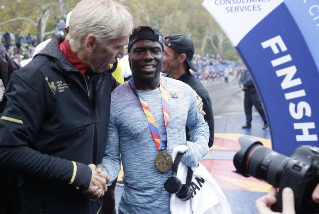 Kevin Hart gets his NYC Marathon medal from NYRR president Peter Ciaccia after he crosses the finish line completing the NYRR TCS New York City Marathon in New York City on Sunday. Photo by John Angelillo/UPI