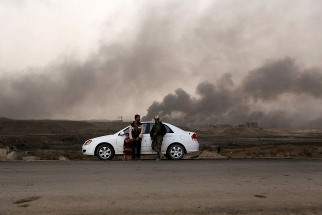 Iraqi security forces have captured about 20 percent of territory in Mosul away from the control of the Islamic State, which is now completely isolated in the east of the city, U.S. military officials said. In this image, Iraqi civilians flee from fighting while the smoke rise in the background from burning oil fields damaged during the fighting between Iraqi forces and Islamic State militants near Mosul on November 1. File Photo by Murat Bay/UPI