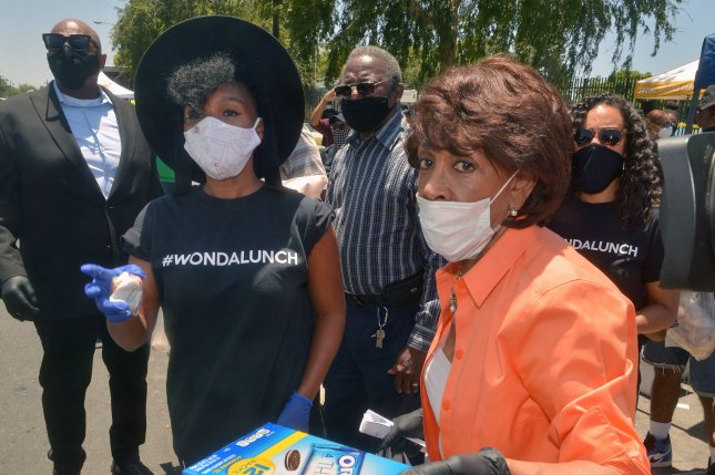 Rep. Maxine Waters, D-Calif., (R) and singer Janelle Monae distribute more than 2,000 prepared meals on Tuesday at Ted Watkins Park in the Watts area of Los Angeles, Calif., to aid residents struggling with the coronavirus crisis. Photo by Jim Ruymen/UPI
