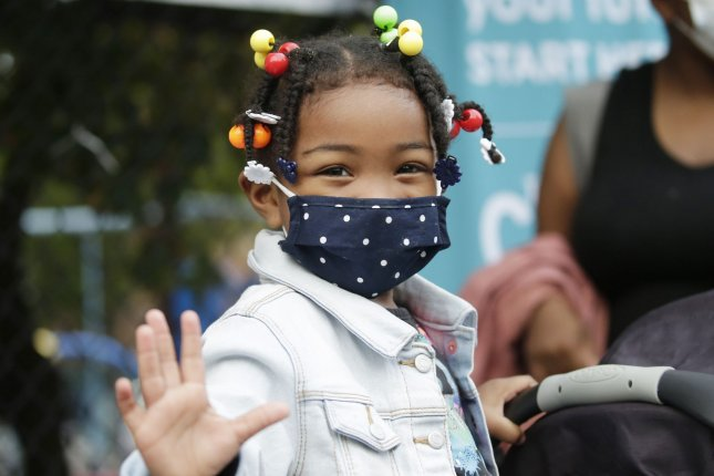 A masked young girl waves before entering The Island School in New York City on September 29. The school, and many others in the city, reopened that day with a combination of blended learning and home schooling. Photo by John Angelillo/UPI