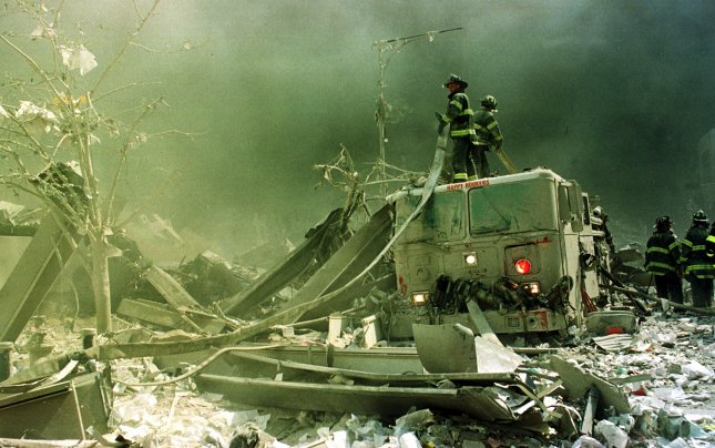 Firefighters stretch a water line to extinguish some of the rubble near the World Trade Center in New York City following the terrorist attack of September 11, 2001. Researchers at Stony Brook University found in a recent study that first responders who have developed PTSD as a result of their efforts on that day and in the months afterward should be monitored for cognitive impairment and dementia. File photo by Monika Graff/UPI