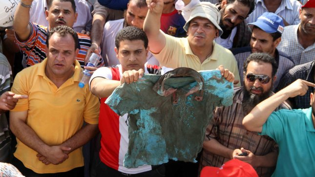 Egyptian supporters of ousted president Morsi show a blood-stained shirt of one of the victims during clashes with Republican Guards forces in Cairo, Egypt, July 08, 2013. UPI/Ahmed Jomaa