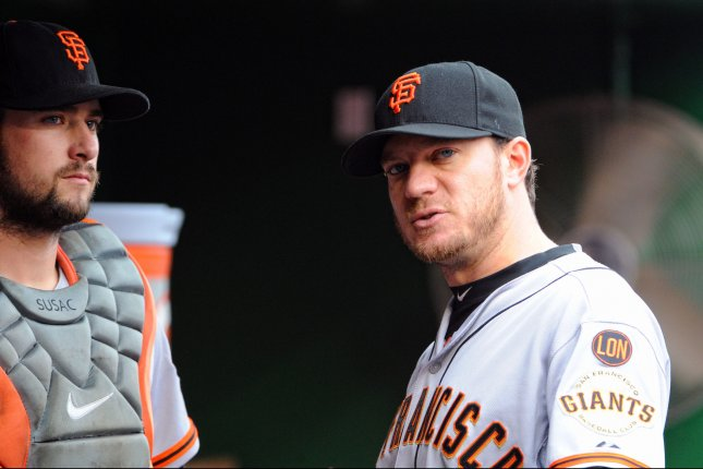 San Francisco Giants starting pitcher Jake Peavy (22) talks with catcher Andrew Susac (34). Photo by Mark Goldman/UPI