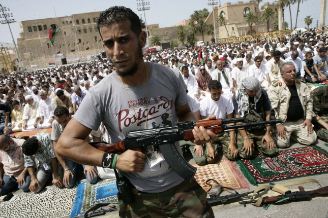 A rebel fighter a guard, while Libyans gather pray Friday in Martyr's Square in the capital Tripoli. Libya, Sept. 2, 2011. Rebel forces are advancing toward Moammar Gadhafi's hometown Sirte despite the extension of a deadline for the town's surrender, rebel officials said Friday. UPI/Tarek Elframawy..