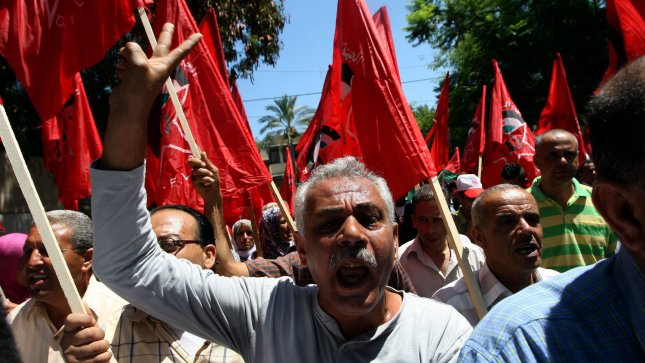 Palestinians chant slogans and wave Palestinian and red flags, background, that represent the Palestinian Marxist-Leninist secular political and military organization, during a demonstration organized by the Democratic Front for the Liberation of Palestine, against resuming peace talks with Israel in Gaza City, July 30, 2013. Israeli and Palestinian negotiators held their first peace talks in nearly three years on Monday in a U.S.-brokered effort that Kerry hopes will end their conflict despite deep divisions. Arabic on the poster reads, No negotiations without a halt a settlements. UPI/Ismael Mohamad
