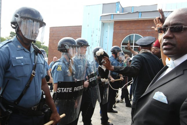 Protesters are greeted by a wall of police officers after a march to the Ferguson Police department in Ferguson, Missouri on August 11, 2014. People are upset because of the Ferguson Police shooting and death of an unarmed black teenager Michael Brown on August 9, 2014. In all about 20 businesses sustained damage after a candlelight vigil turned violent. UPI/Bill Greenblatt