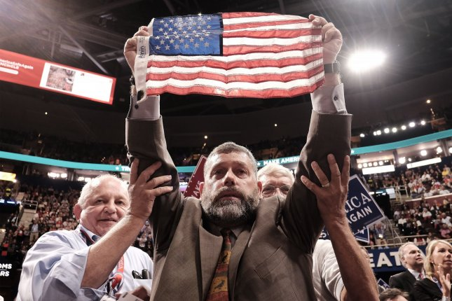 A delegate raises the American flag at the Republican National Convention in Cleveland, Ohio, on July 18, 2016. File Photo by Pete Marovich/UPI