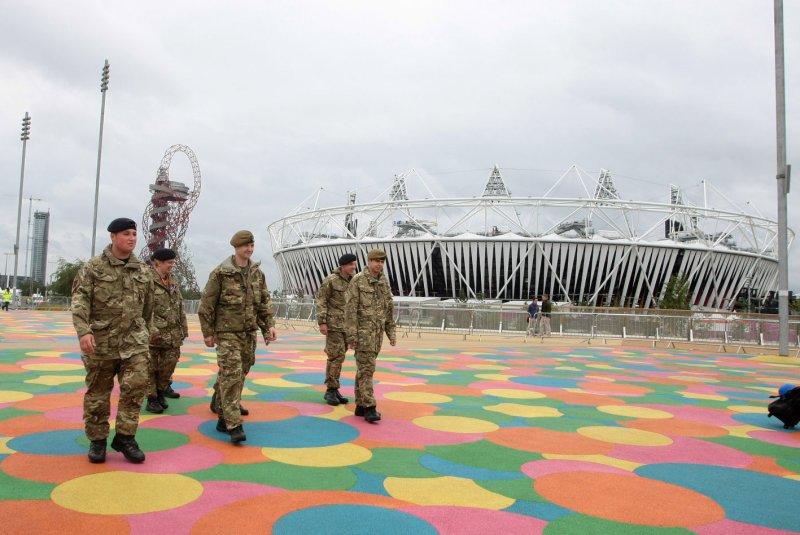 Members of the British military walk past the newly finished London Olympic stadium in Stratford, London, July 16, 2012. UPI/Hugo Philpott