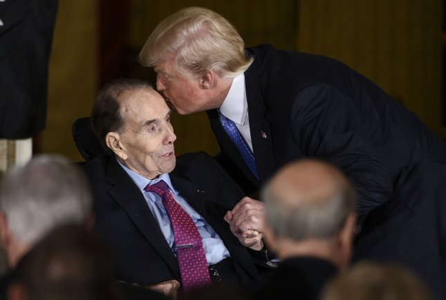 """President Trump kisses World War II veteran and former Senate majority leader Bob Dole as he received the Congressional Gold Medal, the highest civilian honor, in recognition of his service to the nation as a soldier, legislator, and statesman."""" Photo by Leigh Vogel/UPI"""