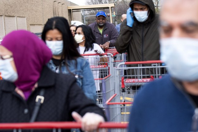 Shoppers wait in line to enter a Costco Warehouse on Friday in Alexandria, Va. Shoppers are continuing to buy and stockpile as the COVID-19 pandemic continues to expand in the United States. Photo by Kevin Dietsch/UPI
