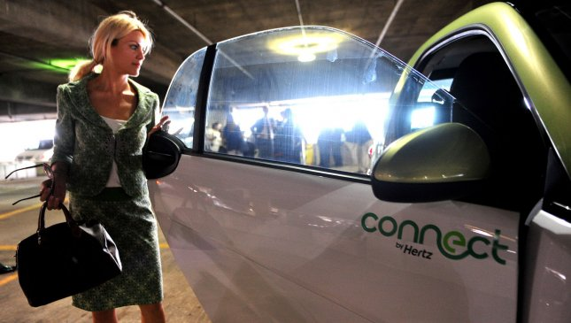 A woman looks at a Smart EV electric car at the unveiling of the Connect Program, a new Hertz Rental Car program allowing people to rent electric and plug-in hybrid vehicles, at Union Station in Washington on May 25, 2011. UPI/Kevin Dietsch