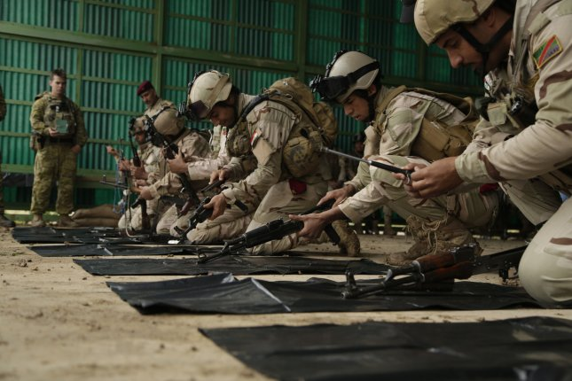 Iraqi soldiers practice disassembling their AK-47 assault rifles for a skills evaluation at Camp Taji, Iraq, on March 28. Photo by Sgt. Paul Sale/U.S. Army